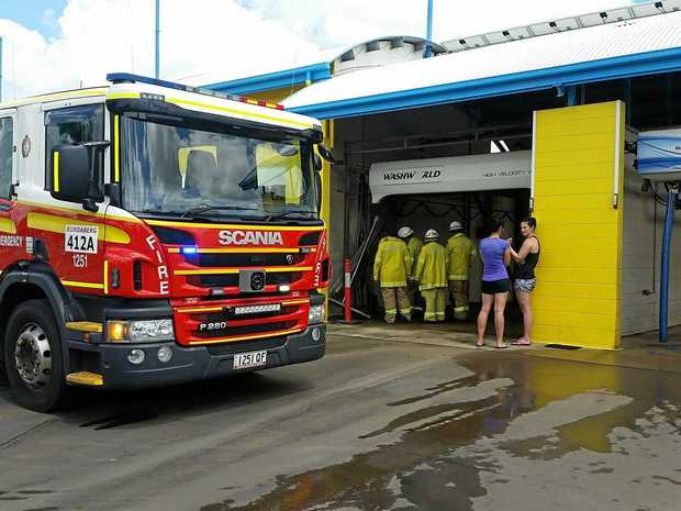 LEG TRAPPED: Emergency services assisted a woman after her car slammed into the side of an automatic car wash bay.