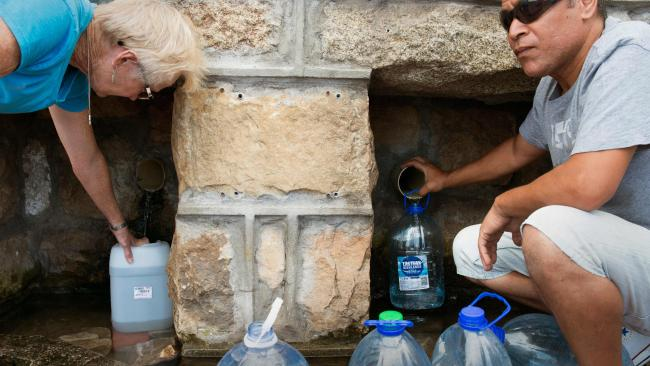 People collect drinking water from pipes fed by an underground spring, in St. James, about 25km from the city centre, on January 19, 2018, in Cape Town. Picture: Rodger Bosch