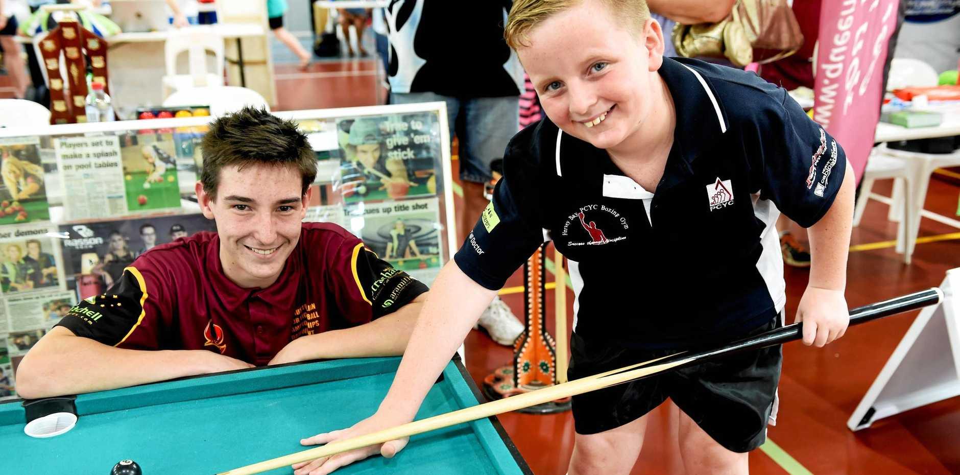 TAKING AIM: Hervey Bay's Joe McClintock and Charlie Hall test their skills at the Fraser Coast Eight Ball stand last year.