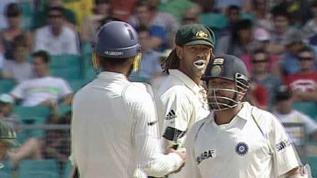 Andrew Symonds (C) looks back at Indian batsman Harbhajan Singh, with Sachin Tendulkar (R) nearby.