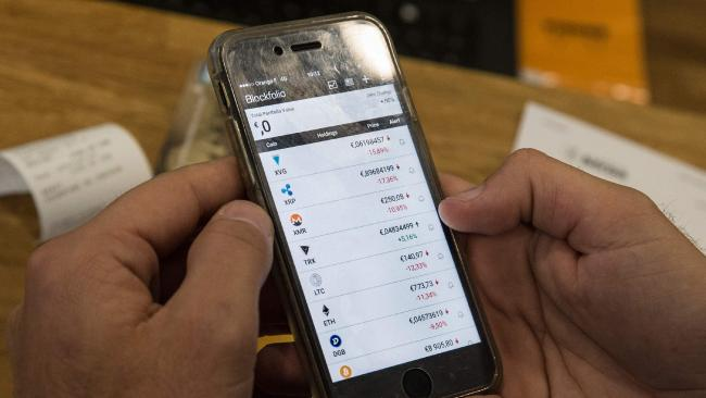 A person looks at a mobile phone displaying virtual currencies exchange rates at La Maison du Bitcoin in Paris on 17 January 2018. Picture: Geoffroy van der Hasselt/AFP