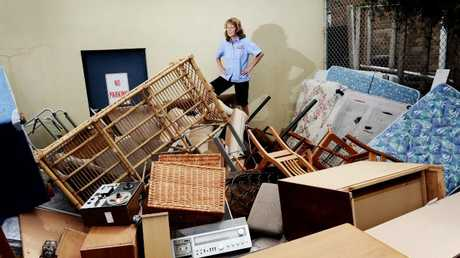 A Salvos store worker stands in a pile of rubbish and unsellable furniture people dump outside.