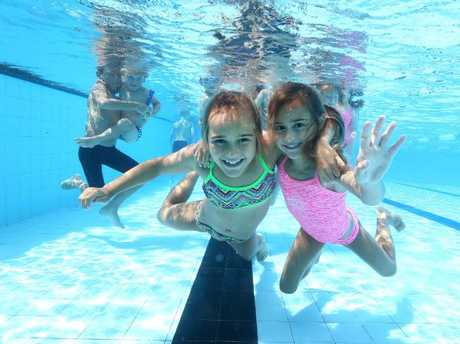 Sisters Ryne, 9, and Kyra Spence, 6, get in the swim as experts urge the State Government to introduce compulsory swimming and water safety lessons to Queensland primary schools. Picture: Adam Head