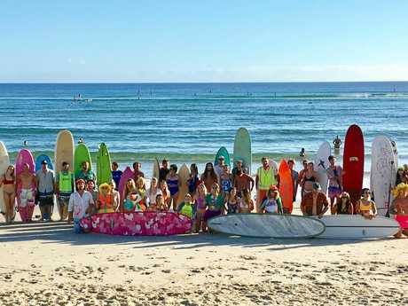Local surfers at the Burleigh Single Fin Fluro Paddle Out to raise awareness of mental health.