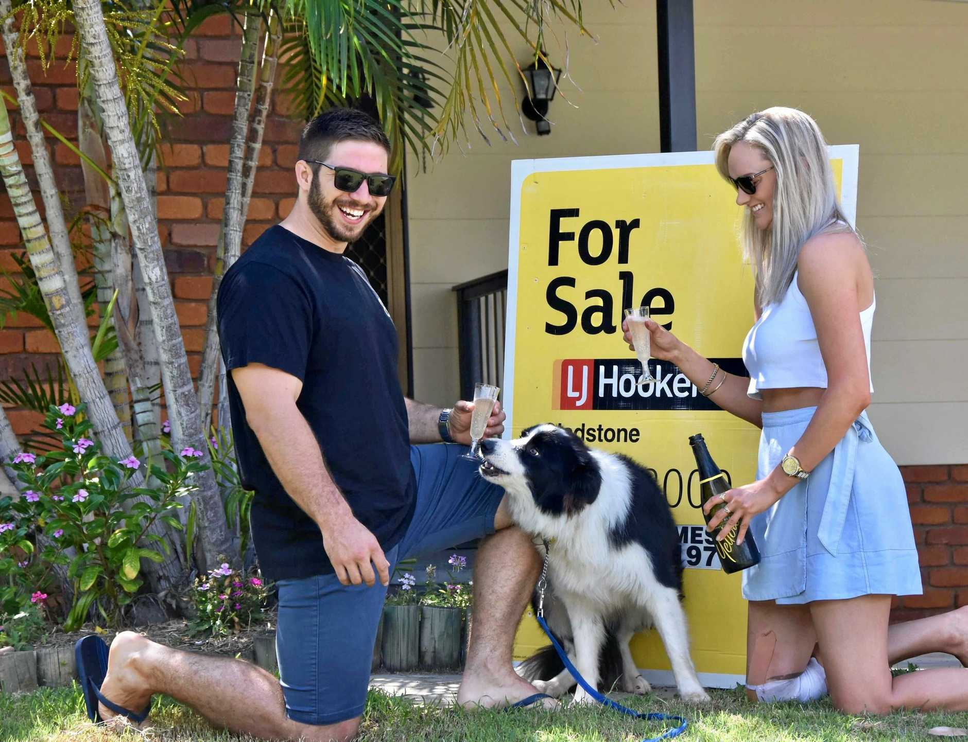 FINALLY: Aaron Cousins and Maddison Smith, with their dog Wilson, have bought their first home after renting in Gladstone for six months.