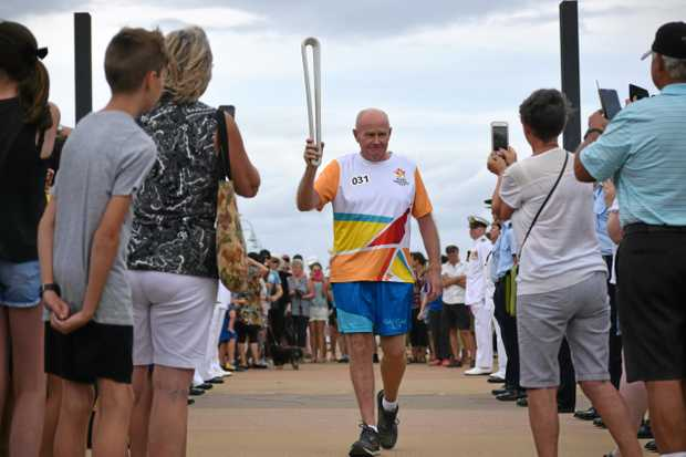 Mick Maley carries the Queen's Baton through the Jetty Foreshores as the relay makes its way toward the Coffs Harbour city centre.