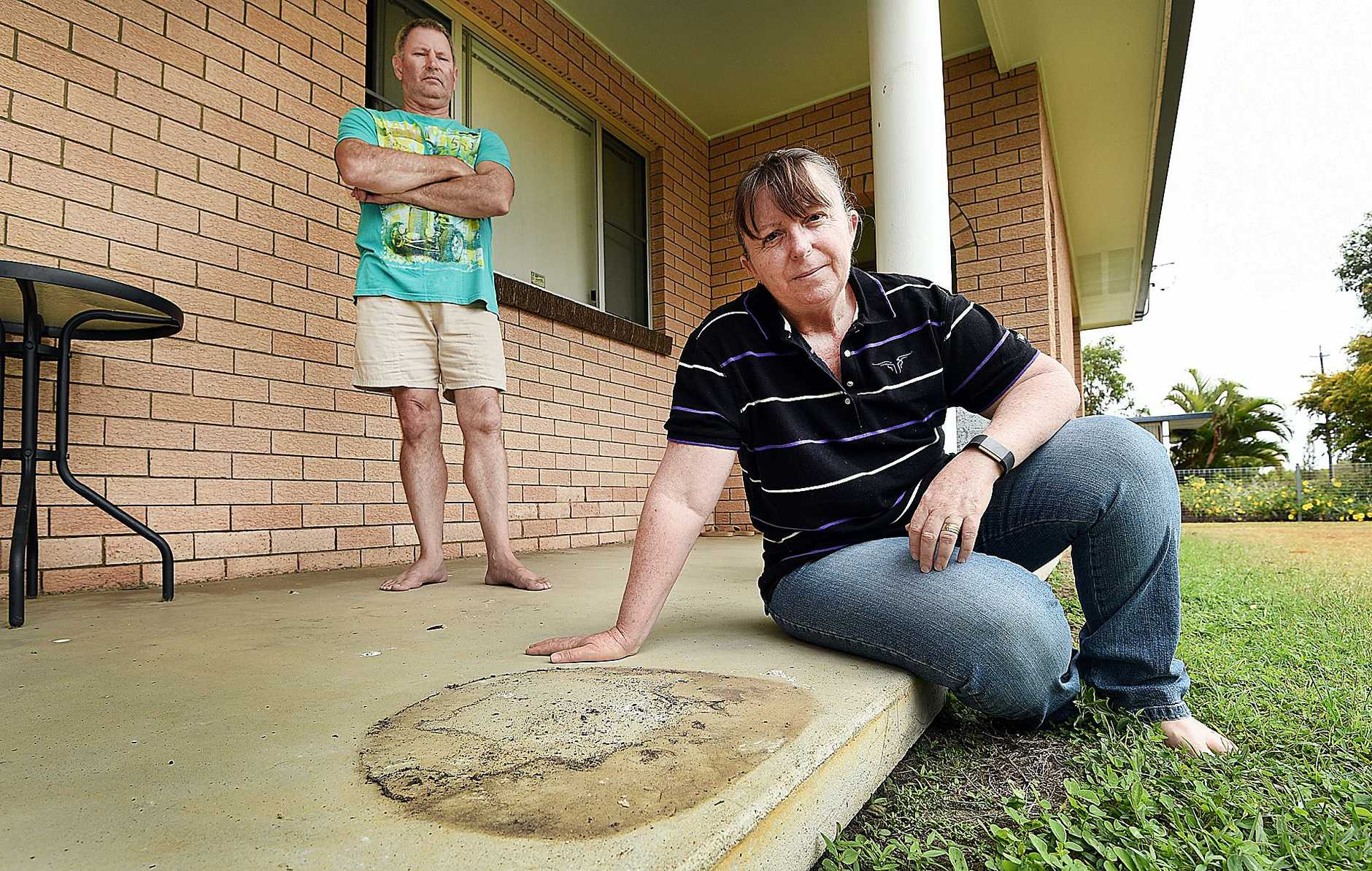 Samantha O'Hanlon and her husband Barry with the spot where their 100 kg concrete statue Pumbaa was stolen from their front porch in Kawungan.
