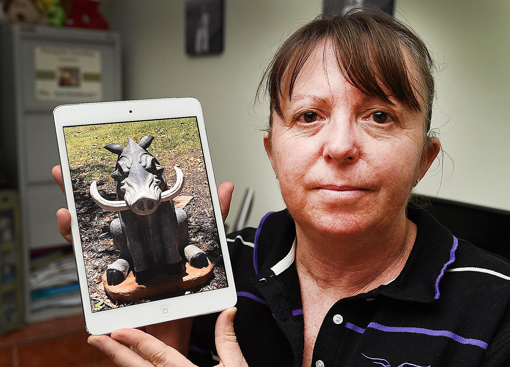 Samantha O'Hanlon with a photo of their 100kg concrete statue Pumbaa which was stolen from their front porch in Kawungan.