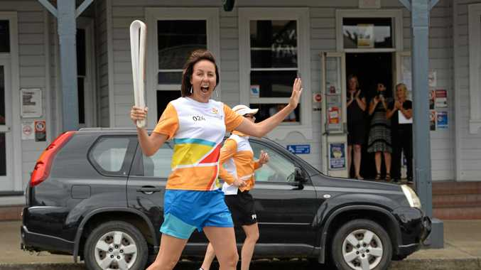 Australian netball legend Liz Ellis is cheered on as she runs down the main street of Bellingen as part of the Queen's Baton Relay.