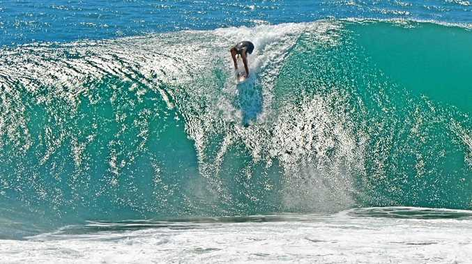 A SURFER takes a monster drop at Sunshine Beach on Wednesday, the day before the swell peaked off the Sunshine Coast.