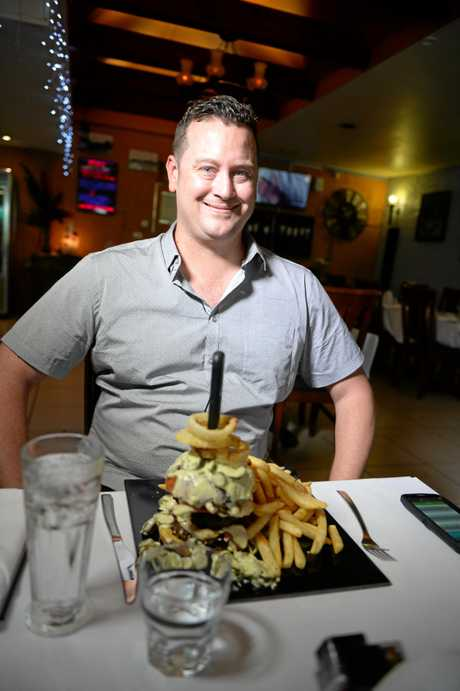 BRING IT ON: The Morning Bulletin journalist Leighton Smith about to take on the 'Norm Challenge Burger'.