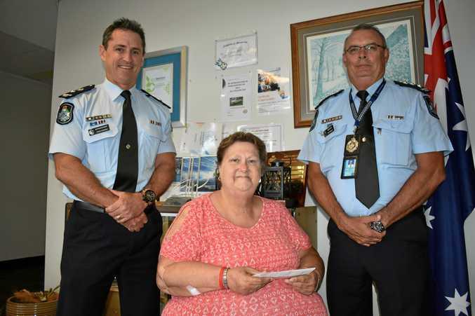 GENEROUS: Superintendent Craig Hawkins and Inspector Pat Swindells handed over almost $300 to pensioner Carol Arthurson.
