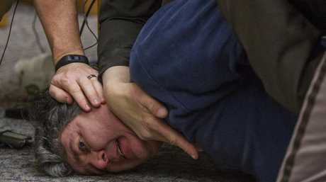 Randall Margraves is pinned to the ground. Picture: Cory Morse/The Grand Rapids Press via AP