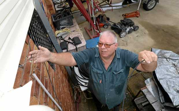 FRUSTING SITUATION: Jeff Beal displays the dodgy wiring going into his property from the stop gap measure to fix his phone line.