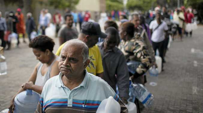 Cape Town residents queue for water, with the daily limit per person reduced to 50 litres.