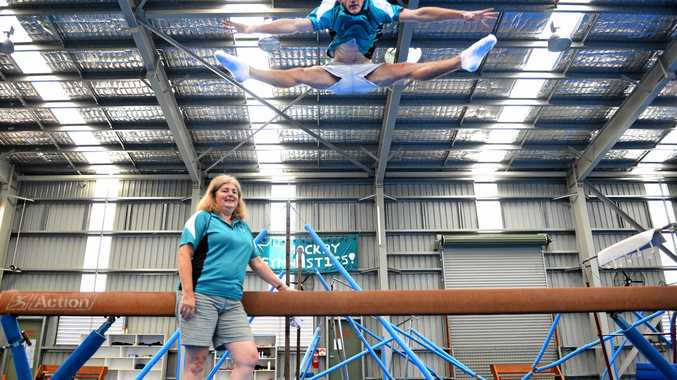 Mackay Gymnastics director of coaching, Michelle Morassi, watches on as boys coach Taz Matsen leaps sky high.
