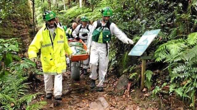 BAD FALL: Volunteers carried an injured woman from Mt Warning on Saturday.