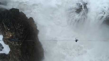 At one point, a crashing wave hits him off, sending him spinning over and over the wire.
