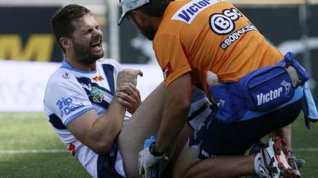 Anthony Don winces in pain after dislocating his shoulder against the Knights last season. Photo: Darren Pateman