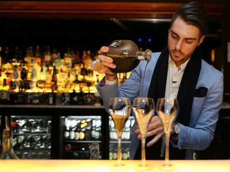 A bartender pours coffee tequila shots at ELEVEN rooftop bar in Fortitude Valley. Picture: Jack Tran
