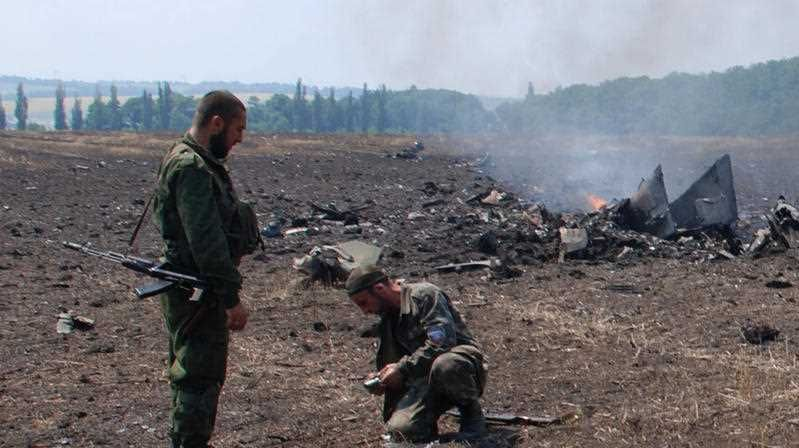 Pro-Russians collect parts of the burning debris of a Ukrainian military fighter jet.