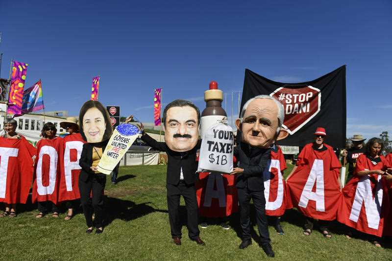 Protesters hold signs and banners at a Stop Adani Mine rally on the lawns of Parliament House in Canberra