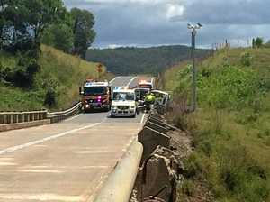 UPDATE: Driver rescued from truck perched on bridge