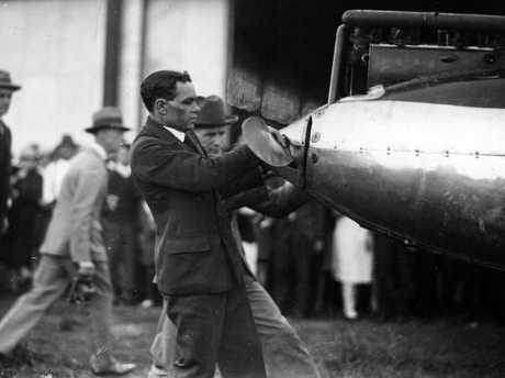 Aviator Bert Hinkler checks his plane at his official welcome to Brisbane after his epic London-to-Australia solo flight in 1928.