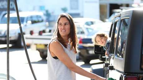 "Jess Walker fills up her ""thirsty"" car with petrol as her son Lachlan watches on at Bargain Petrol station in Erskineville, Sydney. This station has the cheapest petrol around. Picture: Brett Costello"