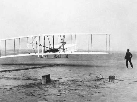 Orville Wright is at the controls of the Wright Flyer as his brother Wilbur Wright looks on during the plane's first flight at Kitty Hawk, North Carolina. Picture: AP Photo/John T. Daniels