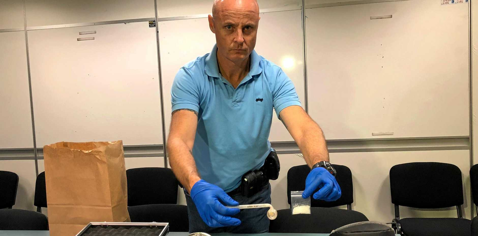 DRUG RAIDS: Senior Constable Christopher Green holds up a pipe and the drug crystal methamphetamine - otherwise known as ice - found during raids of homes across Rockhampton and Gracemere.