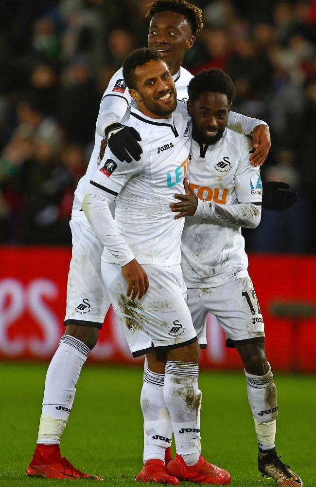 Swansea City's English midfielder Wayne Routledge (C) celebrates with Tammy Abraham and Nathan Dyer.