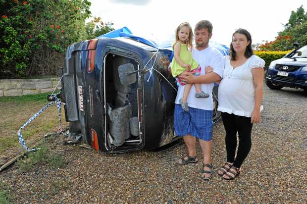 Kerry and Shane Mandrek, with daughter Jessica, stand beside their smashed car. The family has received a $680,000 compensation judgment.