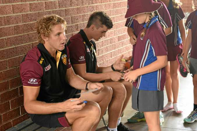 Brisbane Lions players Tom Bell and Ben Keays sign autographs for Yarrilee State School students as part of the AFL's Community Camps in 2016.