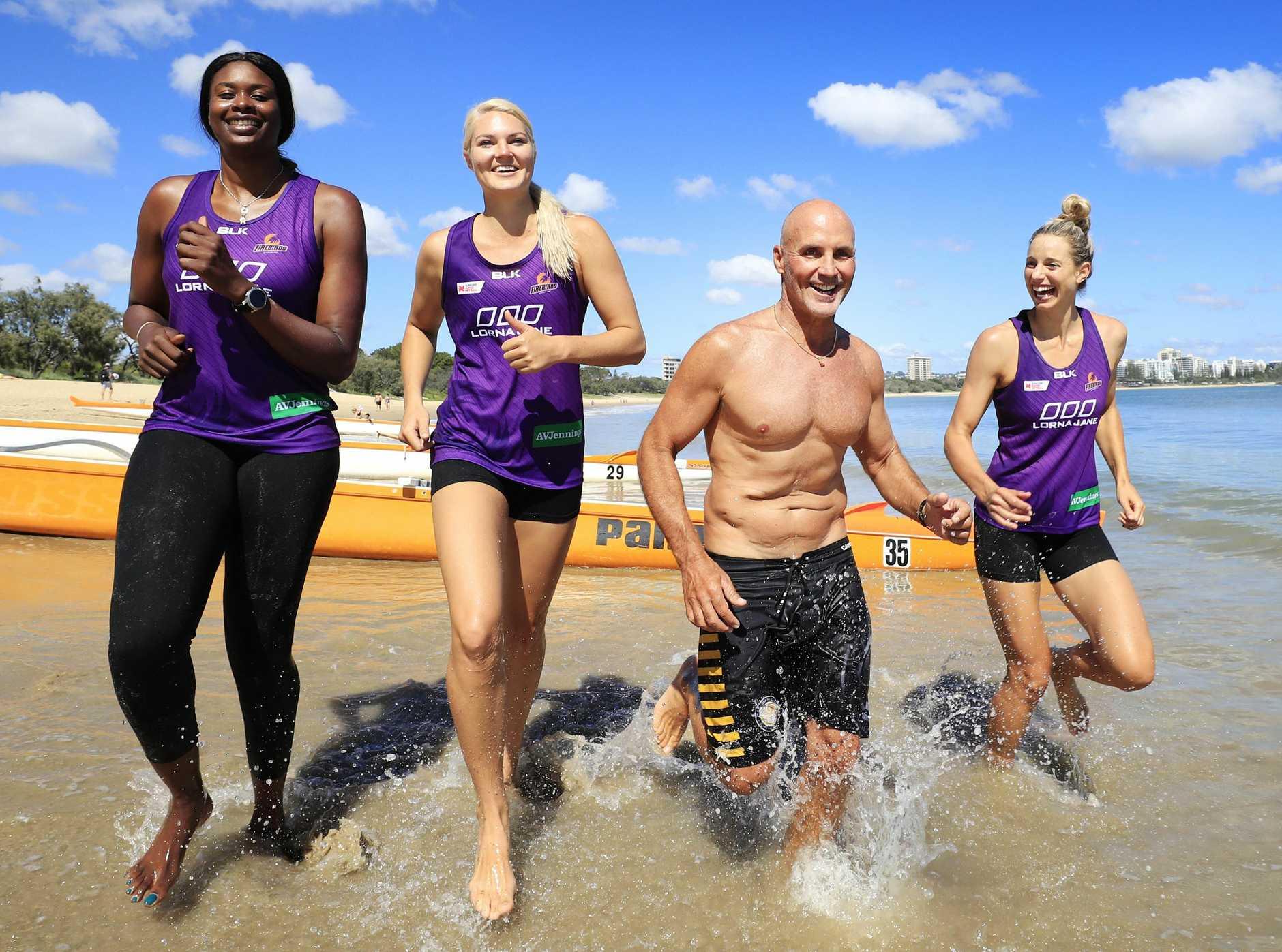 SURF SKILLS: Ironman champ Grant Kenny with Firebirds Romelda Aiken, Gretel Tippett and Laura Geitz.