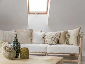 Decorative accessories on wooden table in front of beige sofa with pillows in room on attic