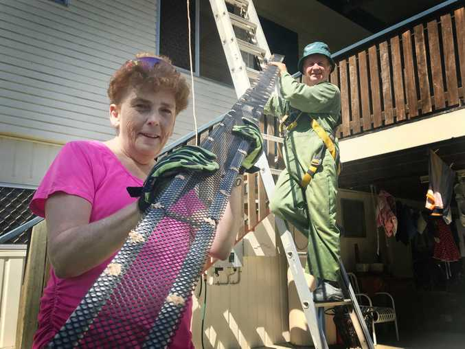 PREVENTION: Phil's Home Maintenance Service owners Phil and Miriam Worsnop with a mesh pipe used to stop pigeons nesting under solar panels.