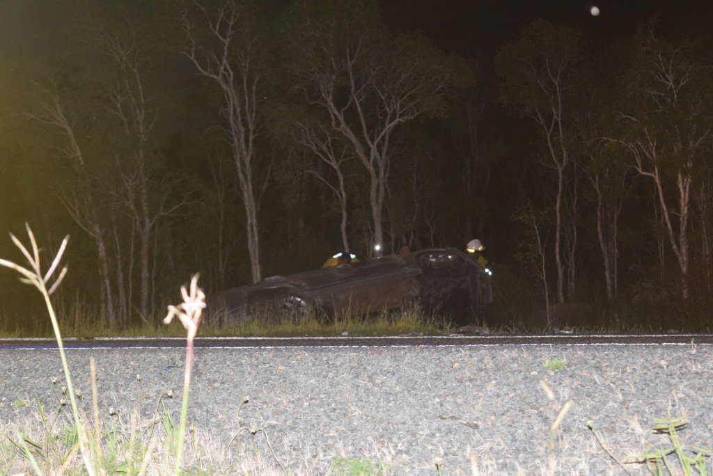SERIOUS CRASH: A silver sedan was pushed into a ravine, upside-down.