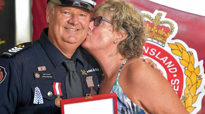 Craig Hogarth gets a kiss from his wife Bev after he was awarded the Commissioner's Medal for Value for rescuing two people from a unit fire in Caloundra.