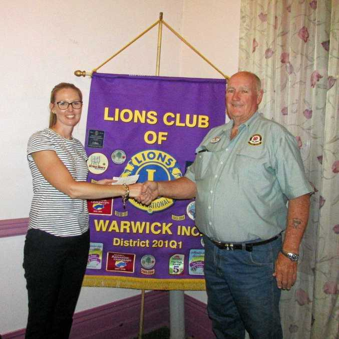 Lions Club Warwick president John Griffith presents RACQ LifeFlight's Amy Luhrs with a cheque for $4000.
