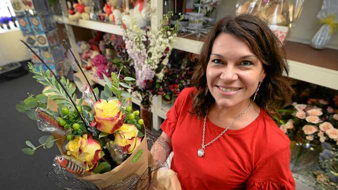 Natalie Swift from Tall Pines Florist with a bouquet of flowers including fishing lures.