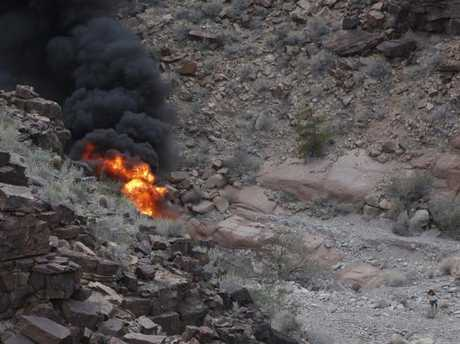 A survivor, lower right, walks away from the scene of the helicopter crash along the jagged rocks of the Grand Canyon, in Arizona. Picture: Teddy Fujimoto via AP
