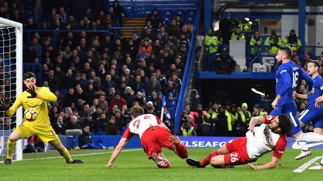 Chelsea's Belgian goalkeeper Thibaut Courtois (L) saves.