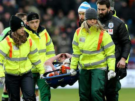 Huddersfield Town's physio covers up Mooy's injury as he leaves the pitch on a stretcher.