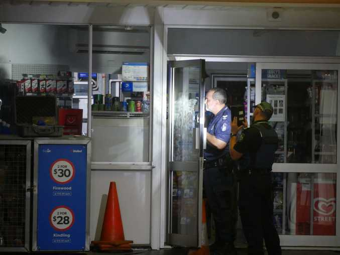 Police officers search for forensic evidence at United Service Station in Eli Waters.