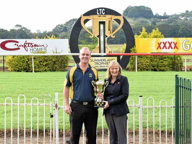 BACK IN THE SADLE: Lismore Turf Club secretary Scott Jones holds the 2017 Lismore Cup with with Council's Events Officer Leanne Clark. Mr Jones who was injured in a gas explosion last year is keen to return to his job and is looking forward to the 2018 event.