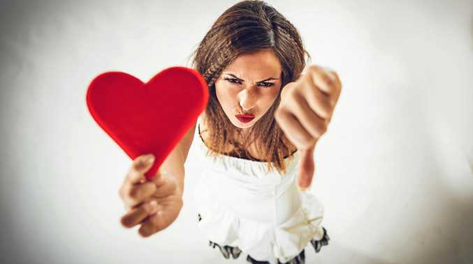 Beautiful displeased girl holding red heart and pointing thumb down. Valentine's Day concept.