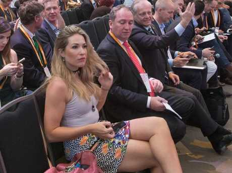 This photo, published by the Daily Telegraph, shows Mr Joyce sneaking a peek at then-media adviser Vikki Campion at a farm summit in Sydney in November 2016.