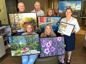 WINDOWS UPDATE: Jim Hourigan from Healing Photo Art (back row, second from left) and Kathryn Blaich (bottom left) with Tuckeroo staff and five of the 30 images that will grace the facility's walls.
