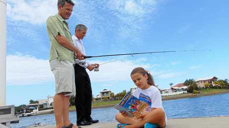 BOOK WORM: Fishing guru Rob Paxevanos and Sunshine Coast division 2 councillor Tim Dwyer wet their lines while Rob's daughter, Hailey, reads some tips from Kids Fishing, the book she and her dad have written.